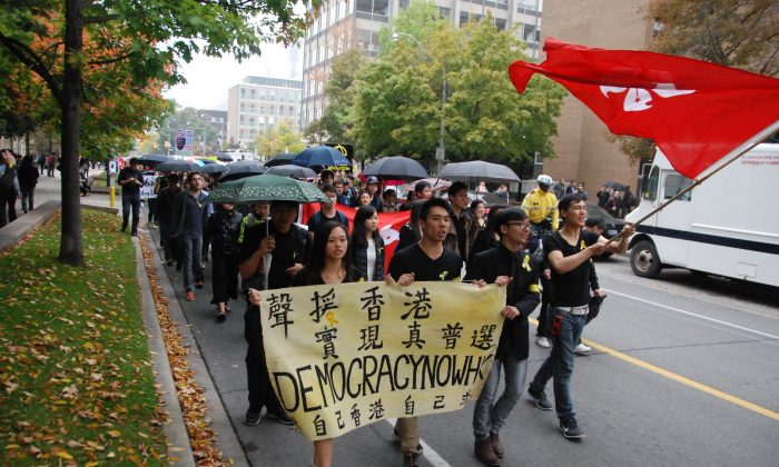 People carry umbrellas on a street in Toronto on Oct. 1, 2014 while demonstrating in solidarity with protesters in Hong Kong. Supporters of democracy took to Hong Kong's streets after the Chinese regime ruled that it would restrict who could run in the 2017 election for the island city's chief executive. (Ling Yi/Epoch Times)