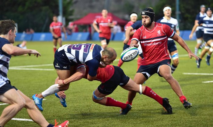 James Richards of Natixis HKFC gets stopped in his tracks by a robust tackle by a Bloomberg HK Scottish defender during their match at Super Saturday on Saturday Sept 27, 2014. HK Scottish edged the match 26-22 to snatch the Broony Quaich trophy away from the Sports Road team. (Bill Cox/Epoch Times)