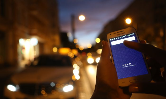 A woman uses the Uber app on an Samsung smartphone on Sept. 2, in Berlin, Germany. Uber, an app that allows passengers to buy rides from drivers who do not have taxi permits, uses a business model that has put it in conflict with the city of Ottawa, which is threatening $20,000 fines. (Adam Berry/Getty Images)