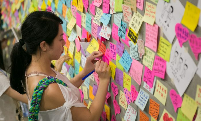 A woman leaves a note on a wall of the Legislative Counsel building in the Admiralty district of Hong Kong on October 2, 2014. (Benjamin Chasteen/Epoch Times)
