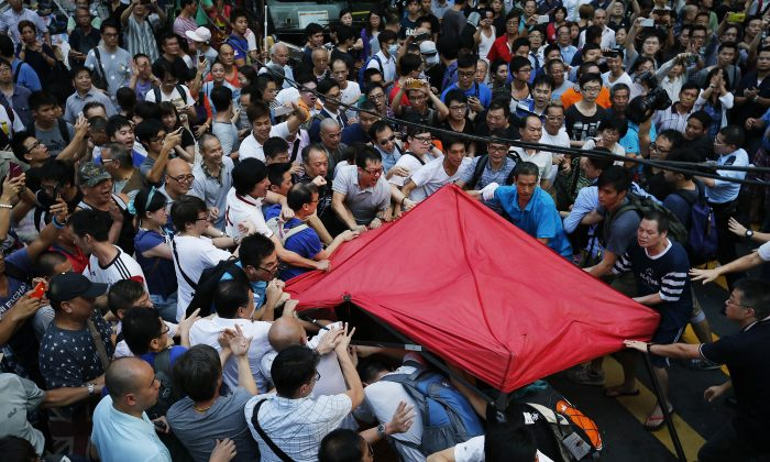 Residents and pro-Beijing supporters tear down a pro-democracy activist tent in Kowloon's crowded Mong Kok district, Friday, Oct. 3, 2014 in Hong Kong. (AP Photo/Wong Maye-E)