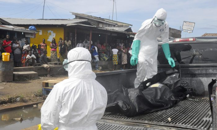 Health workers in protective gear load the body of a woman into a pickup truck in Monrovia, Liberia on Oct. 1 after it was suspected she died from the Ebola virus. The first case of Ebola diagnosed in the U.S. was confirmed in a man who recently traveled from Liberia to Dallas. (AP Photo/Abbas Dulleh)