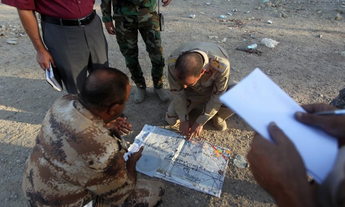 Iraqi army officers look at a map on Oct. 4, 2014, in the Sunni town of Dhuluiyah, some 45 miles north of Baghdad, where security forces, backed by Sunni gunmen fight against ISIL terrorists. (Ahmad Al-Rubaye/AFP/Getty Images)