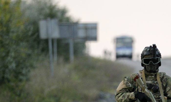 """A world war 3 type atmosphere is increasingly being attached to the Russia-Ukraine conflict, which NATO member states fear could lead to incursions into other countries in addition to creating a buffer zone--""""New Russia""""--for Russia. Here, a Ukrainian soldier stands guard at a road during prisoner exchange near the town of Donetsk, eastern Ukraine, Sunday, Sept. 28, 2014. (AP Photo/Darko Vojinovic)"""