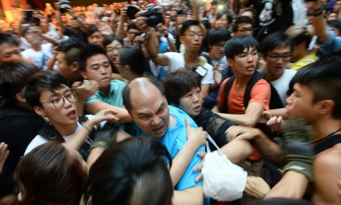 A man (C) pushes towards pro-democracy protesters while several protesters try to hold him back in the Mong Kok district in Hong Kong on Oct. 4, 2014. (Song Xianglong/Epoch Times)