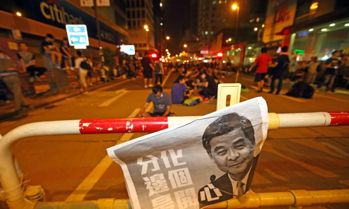 """A poster with Leung Chun-ying's portrait next to Chinese characters that read """"Polarization, who is the happiest?"""" After the protesters in Mong Kok were assaulted, protesting students and citizens were asked to leave for safety reasons, but some still remained on Oct 4, 2014. (Poon/Epoch Times)"""