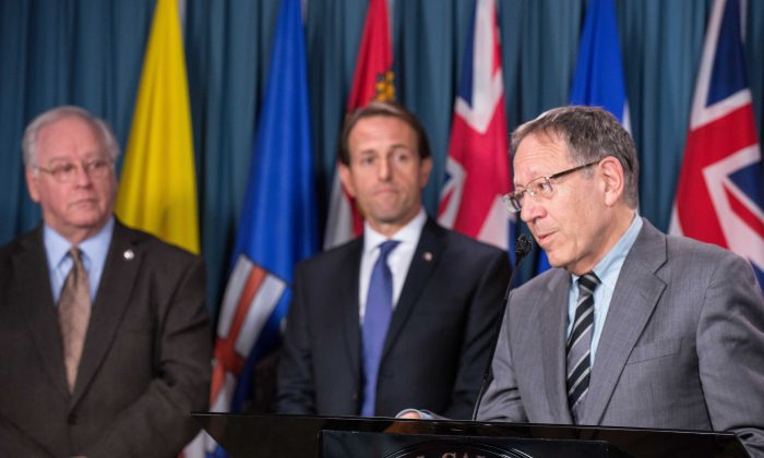 NDP MP Wayne Marston and Conservative MP John Weston look on as Liberal MP Irwin Cotler pleads the case of Iranian Ayatollah Hossein-Kazamani Boroujerdi during a press conference Oct. 7, 2014 on Parliament Hill. Boroujerdi is slated for execution for believing in the separation of church and state. (Matthew Little/Epoch Times)