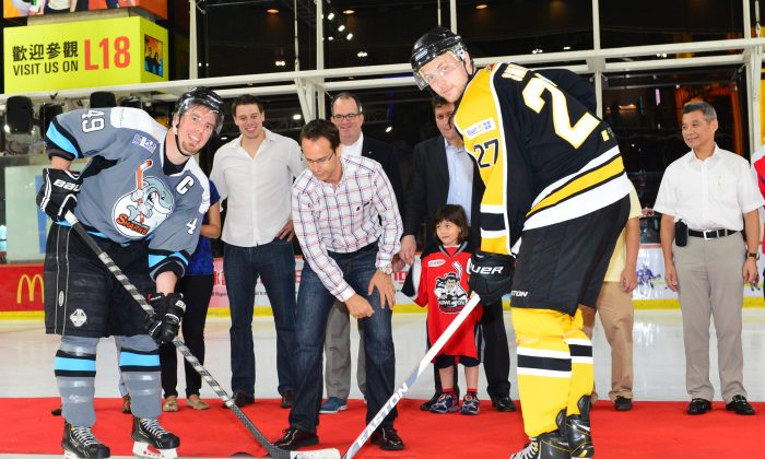 A ceremonial Puck-Drop by John Luciw, kicks off the CIHL 2014 League at Mega Ice on Saturday Oct 4, 2014. Watching the ceremony is J Ian Burchett, Canadian Consul General of Hong Kong and Macau, sponsor representatives and League Officials. (Bill Cox/Epoch Times)