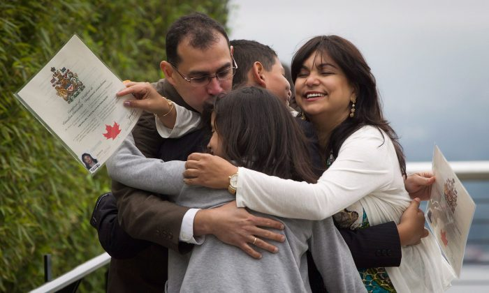 The Pernalete family, originally from Venezuela, engage in a celebratory group hug after being sworn in as Canadian citizens during a special Canada Day citizenship ceremony for 60 people in Vancouver on July 1, 2012. (The Canadian Press/Darryl Dyck)