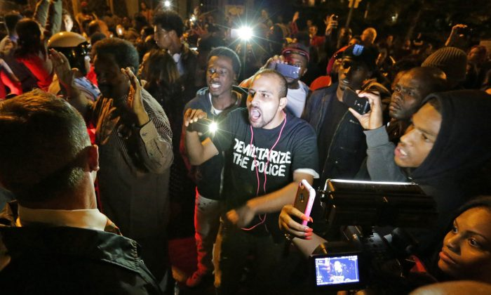Crowds confront police near the scene where a man was fatally shot by an off-duty St. Louis police officer, in south St. Louis, Oct. 8. (AP Photo/St. Louis Post-Dispatch, David Carson)