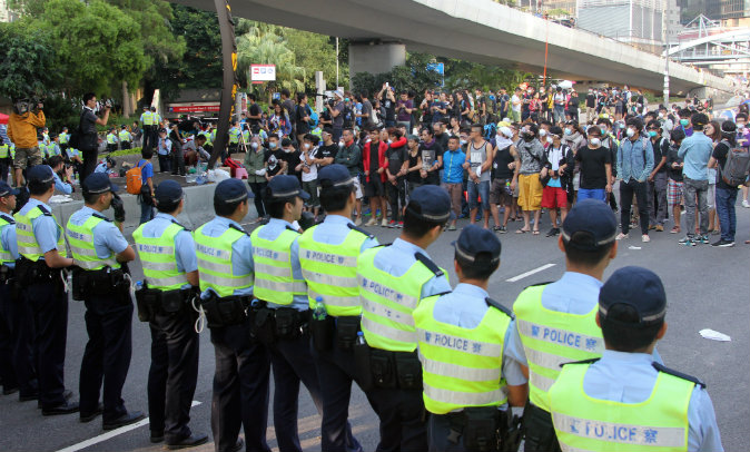 Police officers (front) and pro-democracy demonstrators face off near the government offices in Hong Kong on October 13, 2014. Dozens of Hong Kong police were massing at protest sites where pro-democracy demonstrators have been holding more than two weeks of rallies, paralysing parts of the Asian financial hub. (AFP PHOTO / Laurent FIEVET)