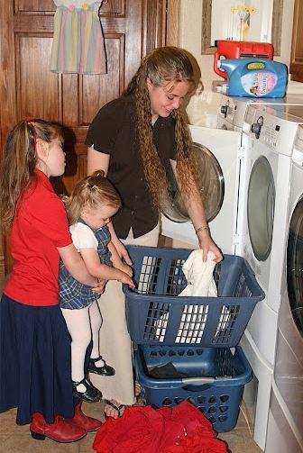Jana Duggar does laundry in an undated file photo with Joy-Ann and Johannah. (Duggar Family)