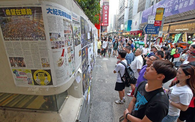 An interested crowd catches up withe the latest news via the Epoch Times. (Poon Zai-shu/Epoch Times)