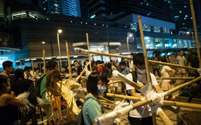 Pro-democracy protesters erect bamboo barricades on October 13, 2014 at Admiralty district in Hong Kong. Pro-democracy supporters continue to occupy the streets surrounding Hong Kong's Financial district after talks broke down with the government. Protesters have threatened to widen their campaign as they continue to call for open elections and the resignation of Hong Kong's Chief Executive Leung Chun-ying. (Photo by Anthony Kwan/Getty Images)