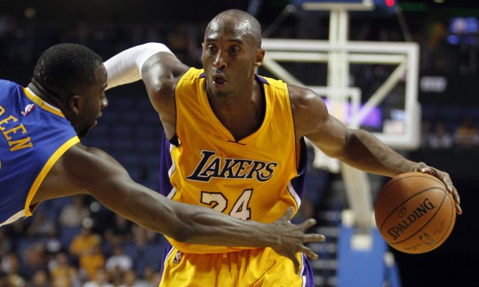 Los Angeles Lakers guard Kobe Bryant, right, drives against Golden State Warriors forward Draymond Green (23) during the first half of a preseason NBA basketball game, Sunday, Oct. 12, 2014, in Ontario, Calif. (AP Photo/Alex Gallardo)