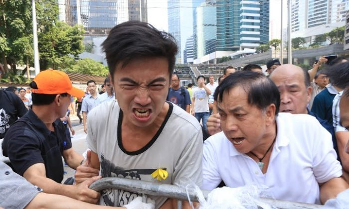Opponents of the occupy movement in Hong Kong launch a coordinated attempt to remove barricades set up by student groups on Queensway, a major thoroughfare in the Central District on Oct. 13, 2014. The group, composed of dozens of men, cut ties holding barricades together and dragged them away. (Yu Kong/Epoch Times)
