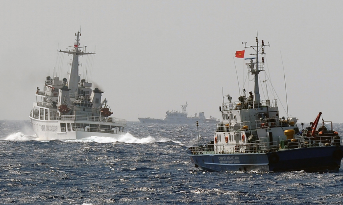This picture taken from a Vietnam Coast Guard ship on May 14, 2014, shows a China Coast Guard ship (L) blocking the way of a Vietnam Coast Guard ship near to the site of a Chinese drilling oil rig (R, background) being installed at the disputed water in the South China Sea off Vietnam's central coast. (Hoang Dinh Nam/AFP/Getty Images)