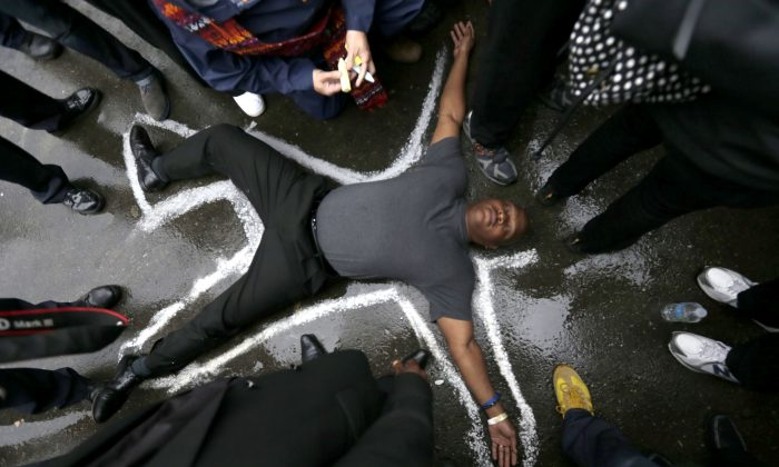Pastor Charles Burton lies on the driveway at the Ferguson, Mo., police station as a chalk drawing is made as a memorial to Michael Brown, Monday, Oct. 13, 2014. (AP Photo/Charles Rex Arbogast)
