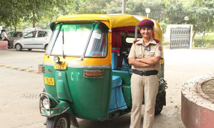 Sunita Choudhary stands in front of her taxi in New Delhi on Oct. 13. Choudhary, who is the first three-wheeled taxi driver in India's capital, escaped from a violent past and now uses her time and resources to help those in need. (Venus Upadhayaya/Epoch Times)