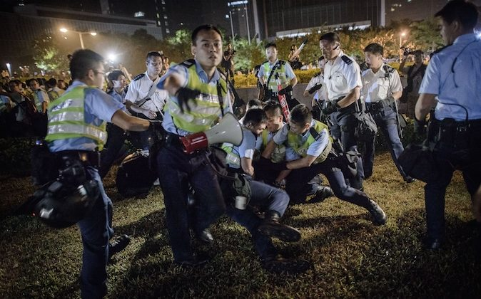 Police forces arrest pro-democracy protesters outside the central government offices in Hong Kong on October 14, 2014. Hong Kong police vowed October 14 to tear down more street barricades manned by pro-democracy protesters, hours after hundreds of officers armed with chainsaws and boltcutters partially cleared two major roads occupied for a fortnight. (PHILIPPE LOPEZ/AFP/Getty Images)