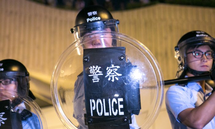 Pro-democracy protesters clash with police after while trying to block off Lung Wo Road, one of the major roadways in Hong Kong, in retaliation after the police removed barriers and opened an occupied road earlier today, on Oct. 14, 2014. (Benjamin Chasteen/Epoch Times)