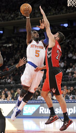 New York Knicks guard Tim Hardaway Jr., left, holds off Toronto Raptors guard Greivis Vasquez as he puts up a shot during the third quarter of a pre-season NBA basketball game Monday, Oct. 13, 2014, at Madison Square Garden in New York. (AP Photo/Bill Kostroun)
