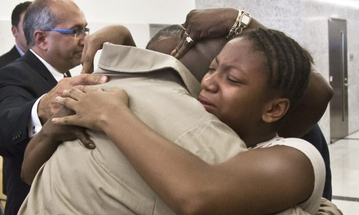 David McCallum, right, hugs family members after his exoneration at Brooklyn's Supreme Court on Wednesday Oct. 15, 2014 in New York.  McCallum and Willie Stuckey, who died in prison, were 16 years old when they were convicted of murder.  A judge exonerated both men for wrongful conviction after nearly 30 years.  (AP Photo/Bebeto Matthews)