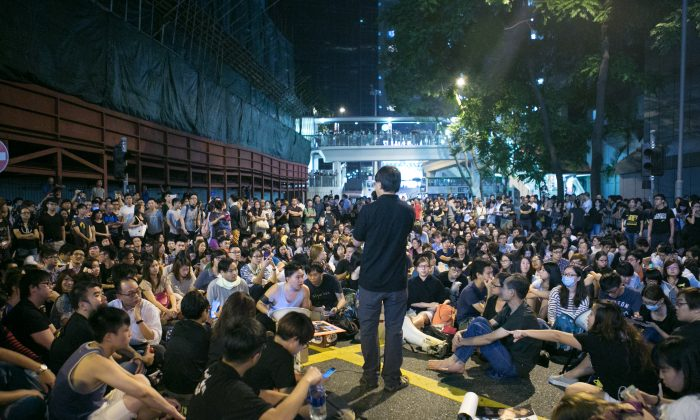 Pro-democracy protesters hold a rally in front of the Hong Kong police headquarters after an earlier incident where the police beat protesters with their fists and batons for taking over a major roadway on Oct. 15, 2014. (Benjamin Chasteen/Epoch Times)