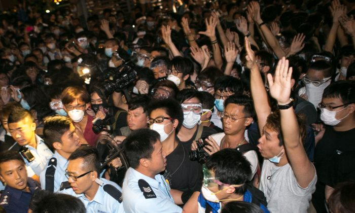 Pro-democracy protesters hold their hands up to show they are unarmed to police officers after they tried to shutdown Lung Wo Road for the second night in a row in Hong Kong on Oct. 16, 2014. (Benjamin Chasteen/Epoch Times)