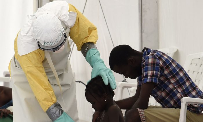 A health worker attends to a girl at the medical centre of Doctor Without Borders (Medecin sans Frontiere (MSF) where people infected with the Ebola virus are treated in Monrovia on Sept. 26, 2014. (Pascal Guyot/AFP/Getty Images)
