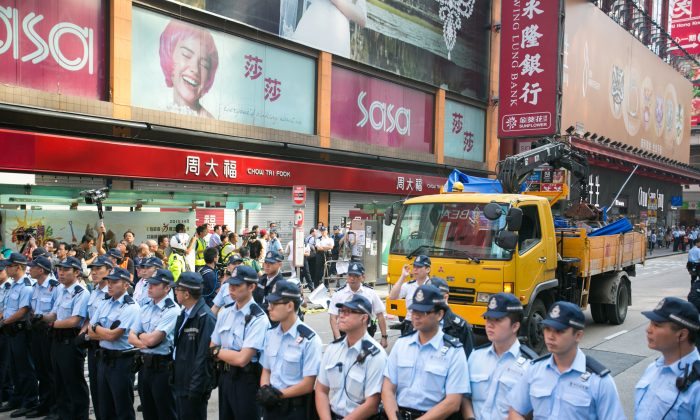 Police and pro-democracy protesters stand off on a small section of Nathan Road after the police came in early in the morning and removed all of the barriers in the surrounding areas in Mong Kok, Hong Kong, on Oct. 17, 2014. (Benjamin Chasteen/Epoch Times)