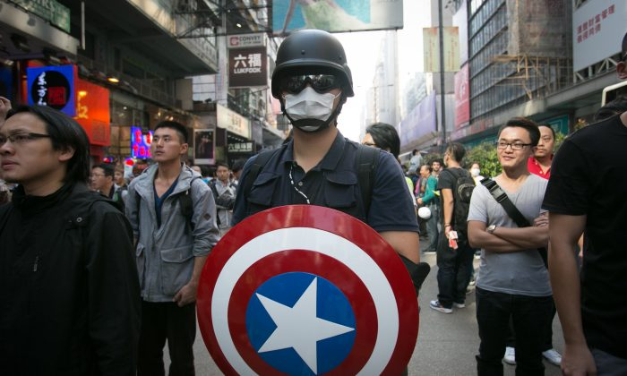 An  pro-democracy activist holds the Captain America sheild a few hours after the Hong Kong police removed all the barriers in the Monk Kok area on Oct. 17, 2014. U.S. government commission (CECC) examines China's commitments to Hong Kong in light of recent pro-democracy protests. (Benjamin Chasteen/Epoch Times)