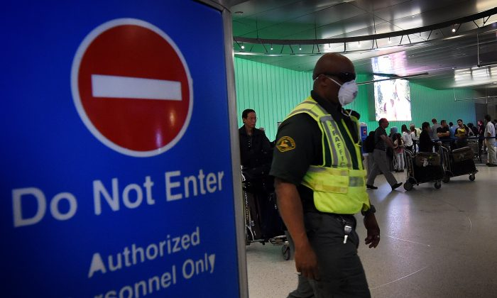 An airport worker wears a protective face mask in the arrivals area of the Los Angeles International Airport  on Oct. 9, 2014. (Mark Ralston/AFP/Getty Images)