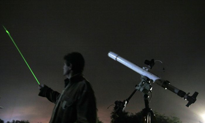 An astronomer observes the night sky for Orionid Meteors as uses a laser pointer to show a radiate at an observatory near the village of Avren east of the Bulgarian capital Sofia, Tuesday, Oct. 20, 2009. The annual Orionid meteor shower is promising to put on a dazzling sky show. The Orionid meteor shower occur each year as a result of Earth passing through dust released by Halley's Comet. The point from where the Orionid meteors appear to radiate is located within the constellation Orion. (AP Photo/Petar Petrov)