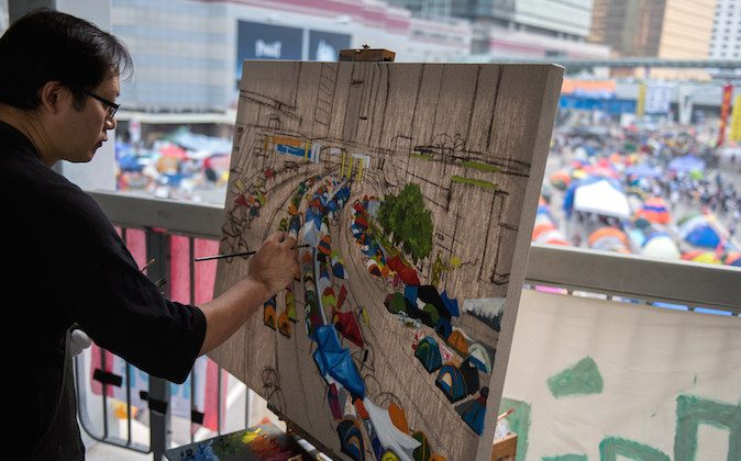 Hong Kong artist Perry Dino paints the pro-democracy protest area next to the central government offices in Hong Kong on October 14, 2014. (Alex Ogle/AFP/Getty Images)