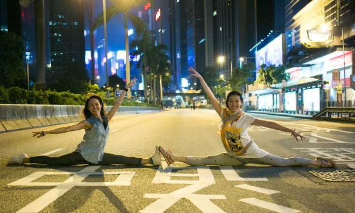 Kitty Lam (L) along with her friend Crystal, do a dance pose in the middle of Harcourt Road, which has been blocked off by protesters on Oct. 12, 2014. Kitty and Crystal both used to do ballet and now they are dance teachers. (Benjamin Chasteen/Epoch Times)