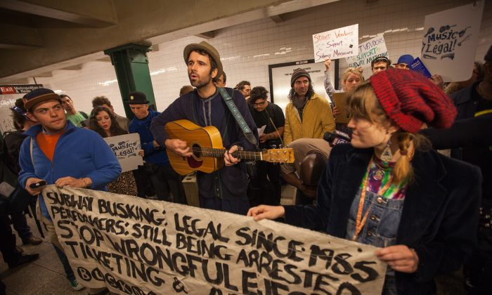 """Andrew Kalleen performs a protest song """"Ohio"""" during a rally against wrongful arrests of subway performers, Metropolitan Avenue subway station, Williamsburg, Brooklyn, Oct. 21, 2014. (Petr Svab/Epoch Times)"""