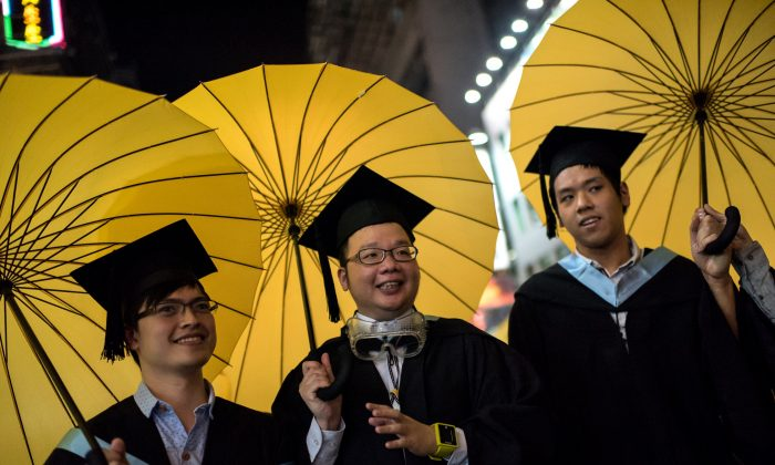 College students in graduation attire carry yellow umbrellas, symbols of the pro-democracy movement in Hong Kong, as they pose for photos in the Mongkok district of Hong Kong on Oct. 19, 2014. Dozens of students held umbrellas during their graduation ceremony at Lingnan University in Hong Kong to urge the head of the school to host talks between the chief executive and the pro-democracy students fairly. (Alex Ogle/AFP/Getty Images)
