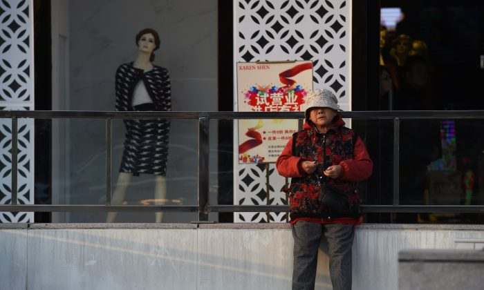 A woman stands near a mannequin in the window of a fashion outlet in Beijing on October 21, 2014. (Greg Baker/AFP/Getty Images)