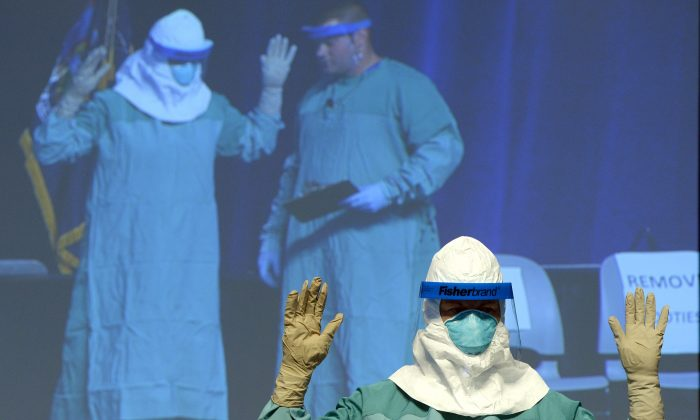 Barbara Smith, RN, Mount Sinai Health Sysytems and Bryan Christiansen MD,(monitor-R) CDC Infection Control Team for the Ebola Response demonstrate the proper technique for donning protective gear during an ebola educational session for healthcare workers at the Jacob Javits Center in New York on October 21, 2014.  (Timothy A. Clary/AFP PHOTO)