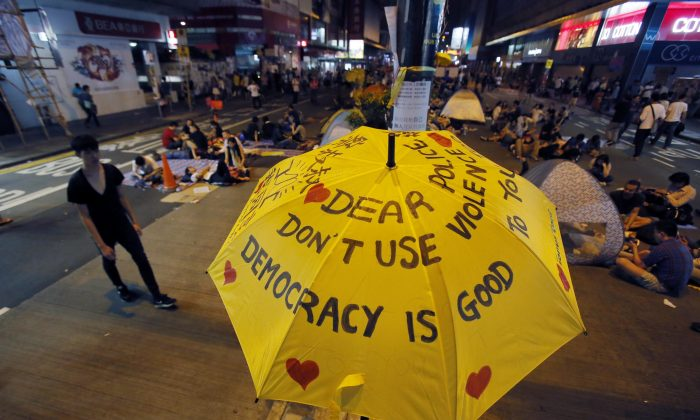 An umbrella, which has become an icon of the protest, reads pro-democracy messages above the student-led protest site in the Mong Kok district of Hong Kong, Monday, Oct. 20, 2014. (AP Photo/Wally Santana)