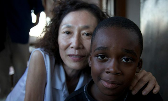 """Director Christine Choy with a Ghanaian boy on the set of """"Ghina."""" (www.filmnewsnow.org)"""