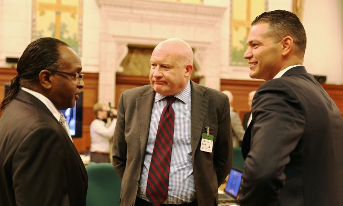 Member of Canada's Parliament, Tyrone Benskin (L) speaks with investigative journalist Ethan Gutmann (C) and Dr. Damon Noto from Doctors Against Forced Organ Harvesting after they testified at the Parliament's human rights subcommittee in Ottawa, Canada on Oct. 21, 2014 (Donna He/Epoch Times)