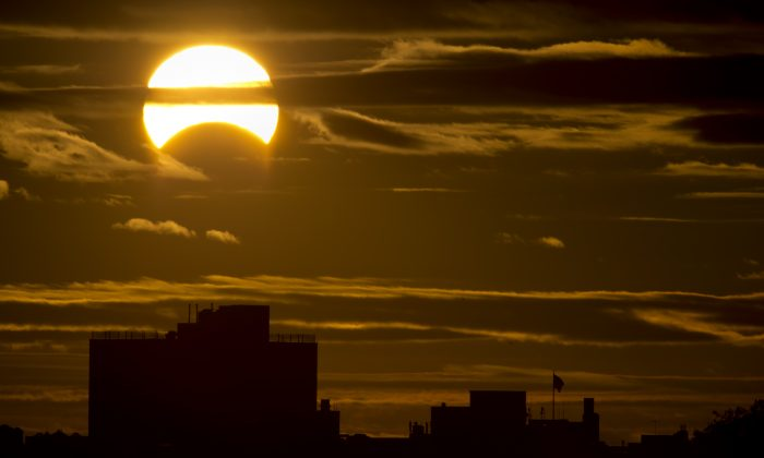 A partial Solar eclipse is seen just after sunrise over the Queens borough of New York across the East River on November 3, 2013 in New York. (/AFP/Getty Images)