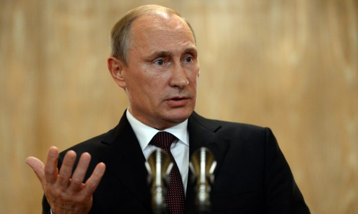 Russian President Vladimir Putin gestures as he speaks at a news conference after the ASEM summit of European and Asian leaders in Milan, Italy, Friday, Oct.17, 2014.  Putin met with Ukrainian President Petro Poroshenko and key Western leaders in an attempt to negotiate a full end to hostilities in Ukraine that could ease sanctions against Russia. (AP Photo/Vasily Maximov, Pool)