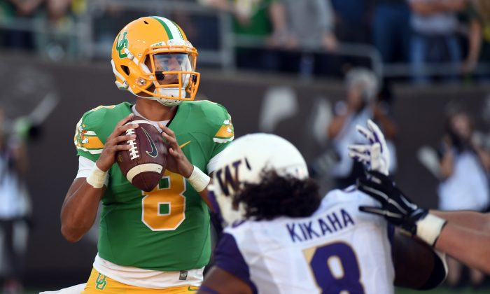 Quarterback Marcus Mariota (L) of the Oregon Ducks drops back to pass as linebacker Hau'oli Kikaha of the Washington Huskies applies pressure in Oregon's 45–20. (Steve Dykes/Getty Images)