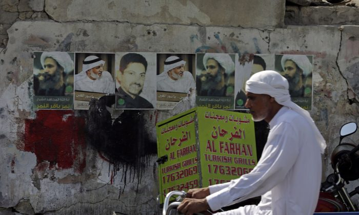 A Bahraini man cycles past images of jailed political activists in the western village of Malkiya, Bahrain, Oct. 15, 2014. PEN Canada has honoured jailed Saudi blogger Raif Badawi with its One Humanity Award. (AP Photo/Hasan Jamali)