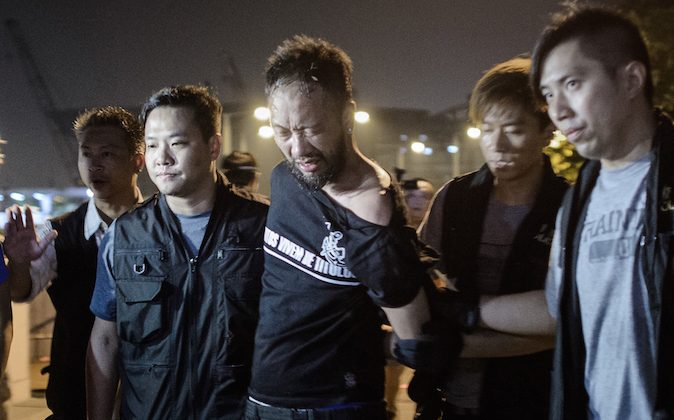 Civic Party member Ken Tsang, one of Hong Kong's pro-democracy political groups, is taken away by policemen, before being allegedly beaten up by police forces as seen on local TV footage shot outside the central government offices in Hong Kong on early October 15, 2014. (Philippe Lopez/AFP/Getty Images)