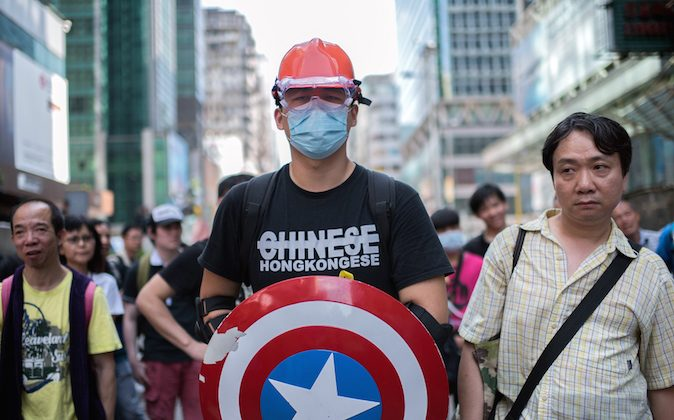 """A man wearing protective gear and carrying a shield from the """"Captain America"""" comic book series stands guard next to a pro-democracy protest barricade in the Mongkok district of Hong Kong on October 19, 2014. (Alex Ogle/AFP/Getty Images)"""