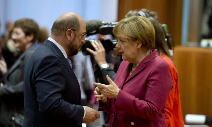 German Chancellor Angela Merkel (R) talks with European parliament president Martin Schulz before a round table as part of a European summit at the EU headquarters in Brussels on October 23, 2014. The two-day summit of the European Council in Brussels will focus on an ambitious package of climate change targets for 2030 but also tackle the Ebola crisis, economic stagnation, concern over Ukraine and tension in Cyprus over Turkey.  (Alain Jocard/AFP Photo)